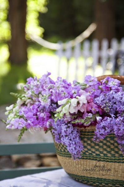 A basket filled with bright-colored flowers makes for a classic centerpiece (Photo courtesy of French Country Cottage)