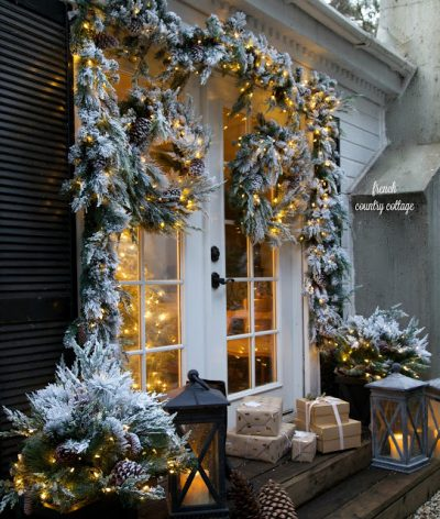 Caption: Frosted greens and merry lights frame this doorway (Photo courtesy of French Country Cottage)