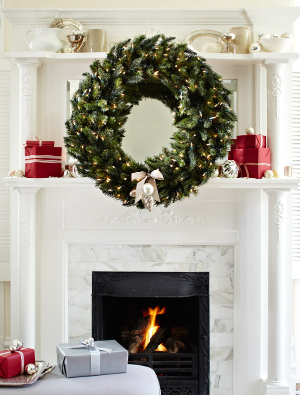 large wreath over a mantelpiece flanked by red gifts