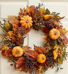 An autumn wreath featuring preserved pumpkins, gourds, berries, and dried autumn leaves