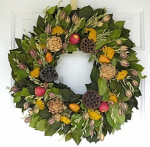 An autumn harvest wreath with faux apples, pears, and artichokes