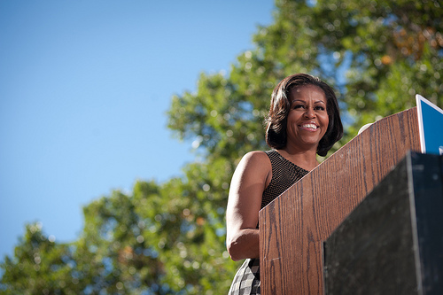 a radiant Michelle Obama addresses a crowd regarding her policies