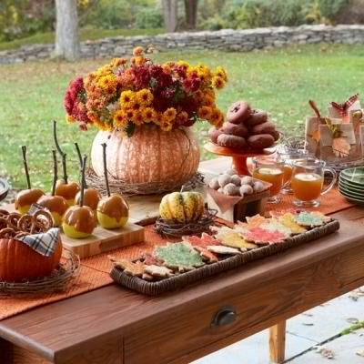 Fall party table with a pumpkin flower vase, caramelized fruits, donuts and apple cider drinks.