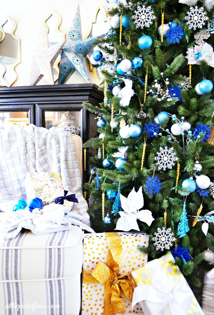 traditional green artificial Christmas tree decorated with blue, gold and white ornaments