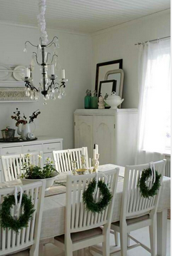 a simple dining space made beautiful by Christmas wreaths