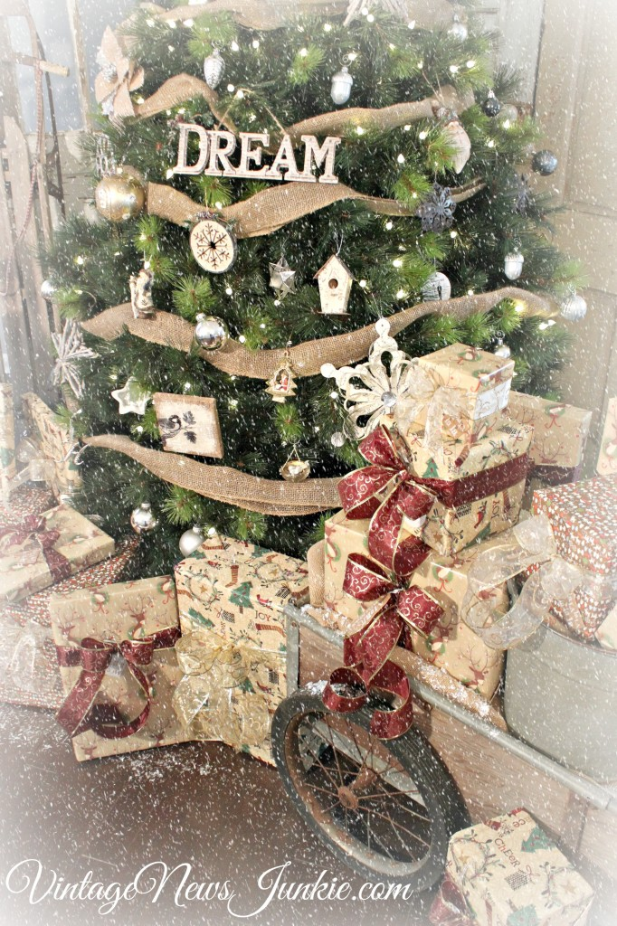 artificial christmas tree decorated in vintage style with a burlap ribbon and rustic ornaments