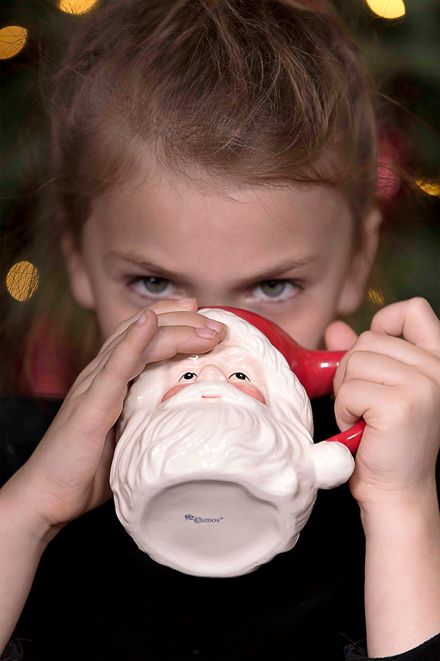 Young girl drinking from a Santa Claus mug