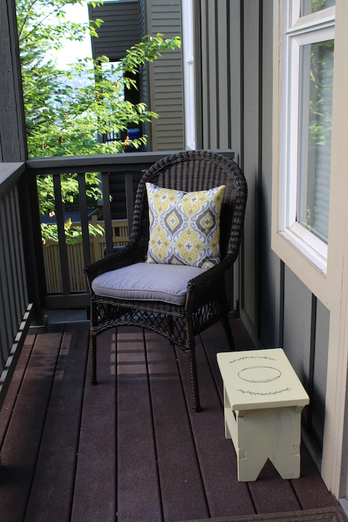 porch decorated with yellow pillow and stool