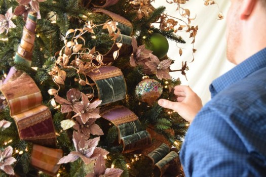 Brad carefully positioning ornaments and accents