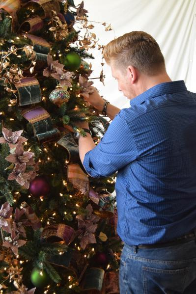 Brad putting the finishing touches on a tree beautifully adorned with ribbon