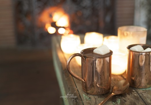 Hot chocolate and marshmallows in burnished copper mug, displayed in front of the fire