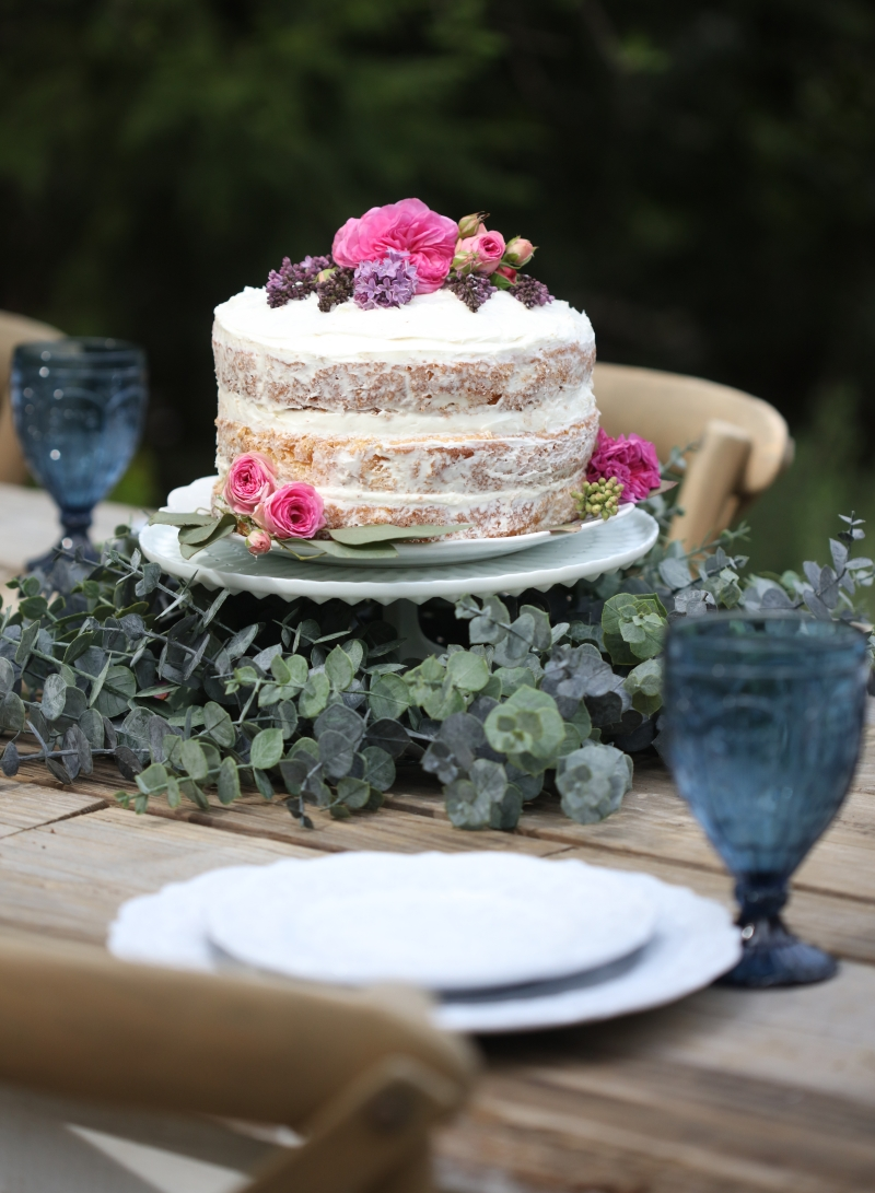 Cake on a pedestal, decorated with Balsam Hill's eucalyptus wreath