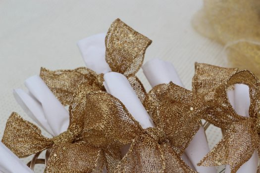 Gold ribbon tied into napkin bows