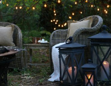 Candle-lit lamps brighten an outdoor space