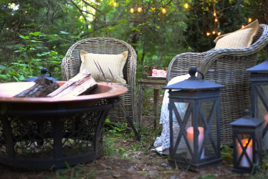 Cozy wicker chairs positioned around a copper firepit