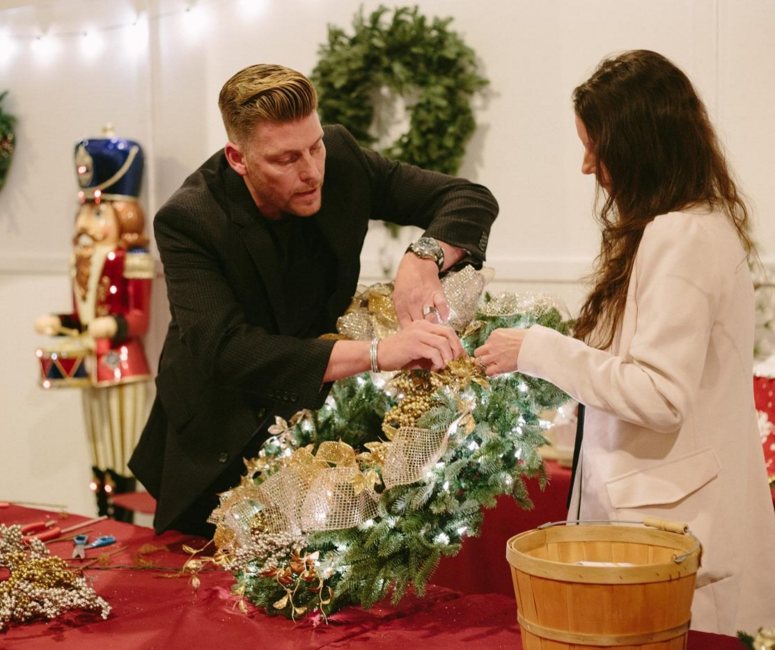 Courtney of French Country Cottage and Brad Schmidt sprucing up a pre-lit wreath in metallic accents