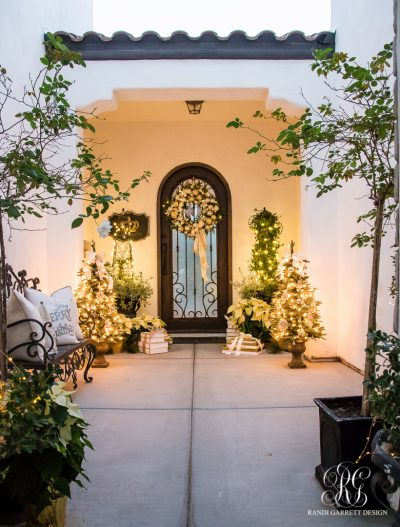 Her classic neutral porch embellished with gold and silver ornaments and lit by Christmas foliage (Photo courtesy of Randi Garett Design)