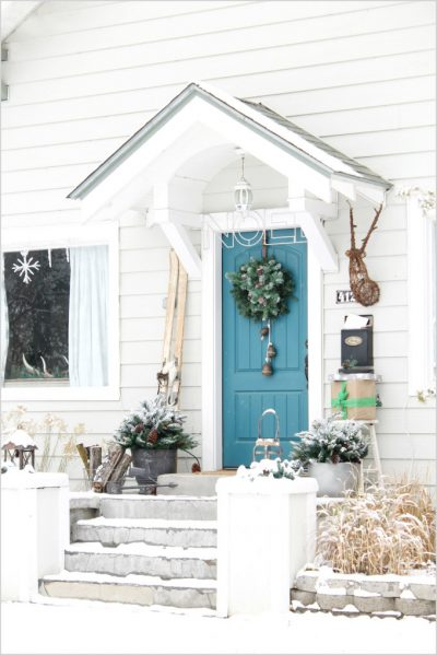 Antiques and greenery add personality to this rustic white porch (Photo courtesy of The Wicker House)