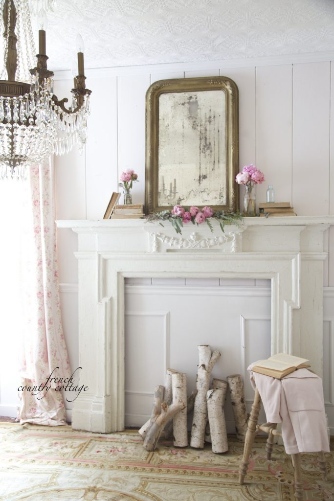 A white mantel is adorned with pink peonies and simple greenery