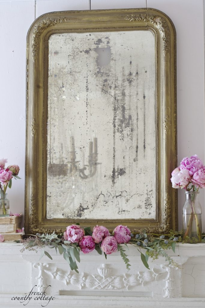 Pink peonies and simple greenery sit around a vintage mirror atop a white mantel