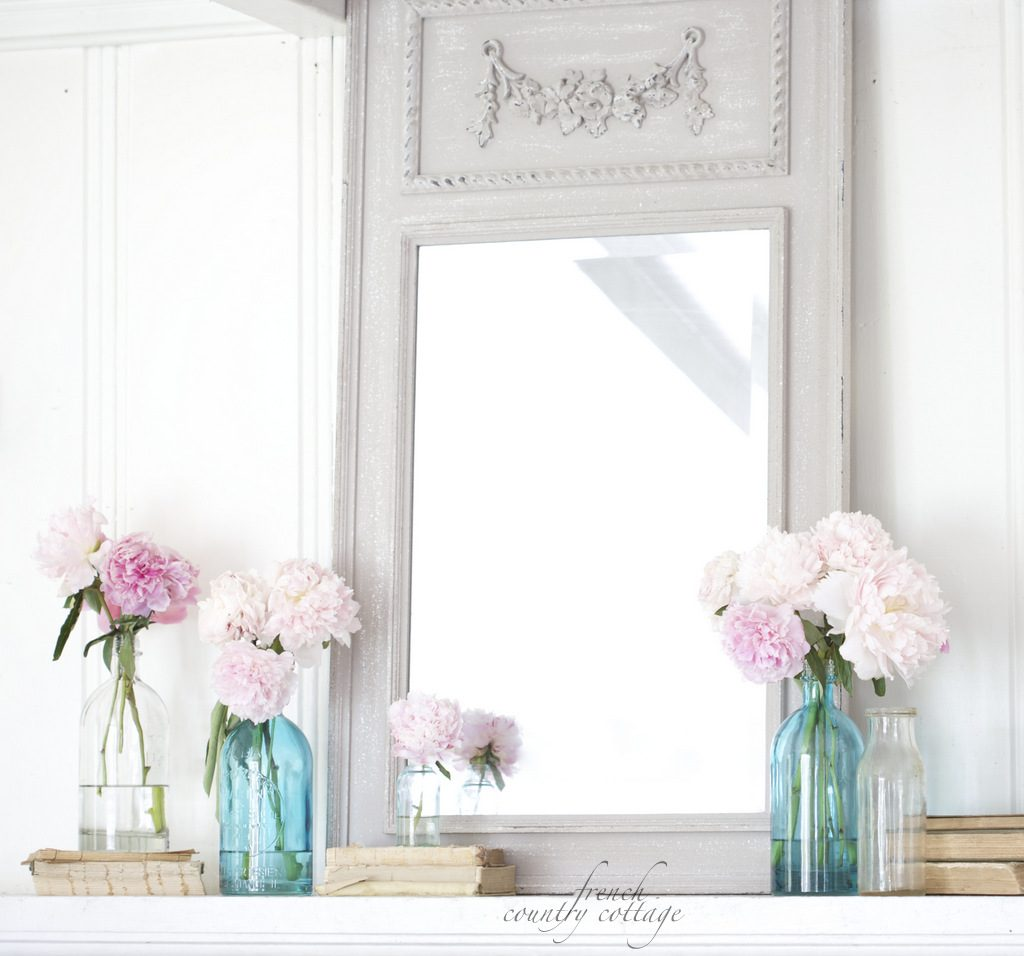 Pastel pink peonies sit in clear and blue glass vases atop a grey mantel