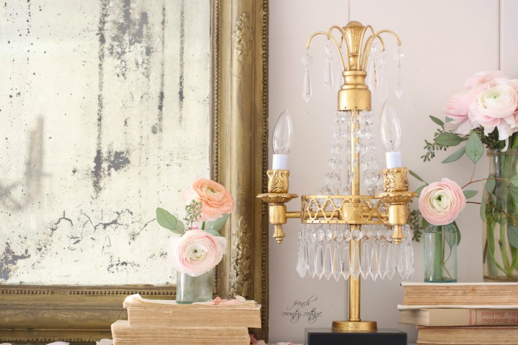 Pastel pink Italian ranunculus sit in glass jars atop old books and a vintage-inspired gold lamp