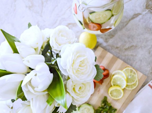 Artificial white tulip and ranunculus centerpiece alongside fruit and vegetable accents arranged on dining table