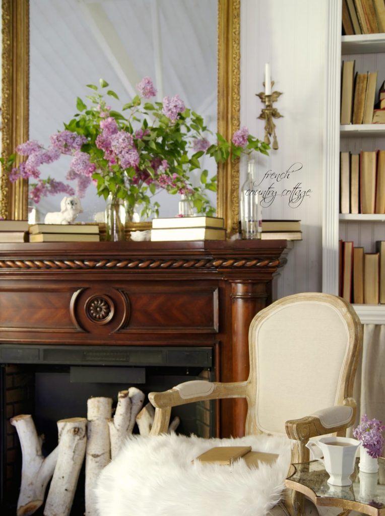 Purple lilacs sit atop a dark brown mantel with neutral decor accents