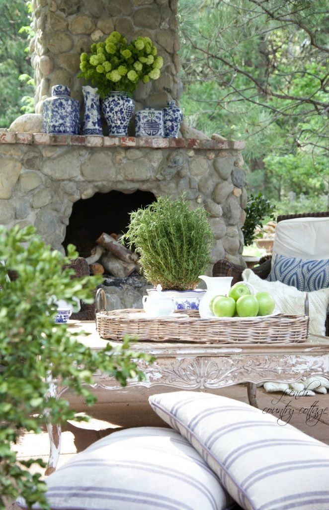 Green hydrangeas fill decorative blue and white containers in an outdoor mantel setting