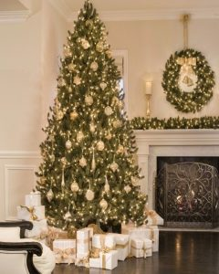 christmas tree set up beside mantel with wreath and garland