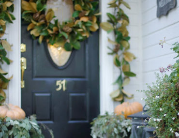 Front door with magnolia foliage wreath and garland and pumkins