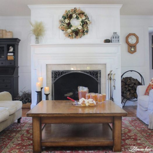 The pretty Heirloom Pumpkin and Magnolia Wreath adding color and texture to a pristine mantel