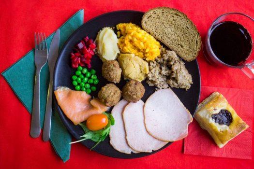 A traditional Finnish Christmas dinner consisting of sliced baked ham, smoked salmon, lihapyorykoita (meatballs), lanttulaatikko (rutabaga casserole), mixed beetroot salad, and puff pastry.