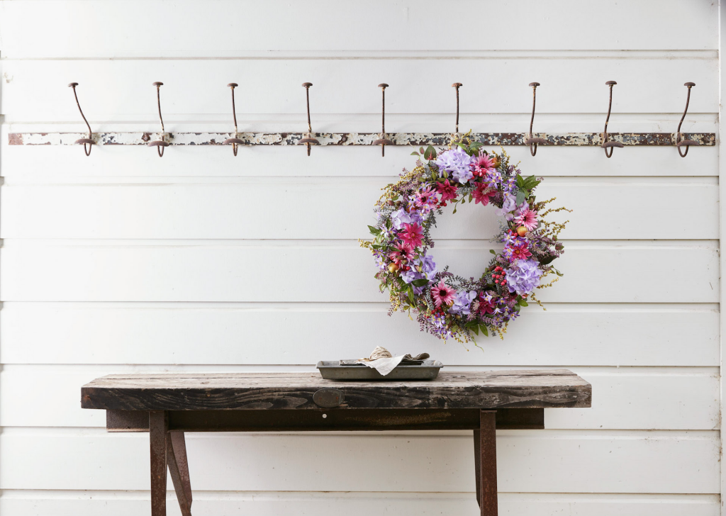 The Vibrant Summer Bloom Wreath hanging from an indoor coat rack.