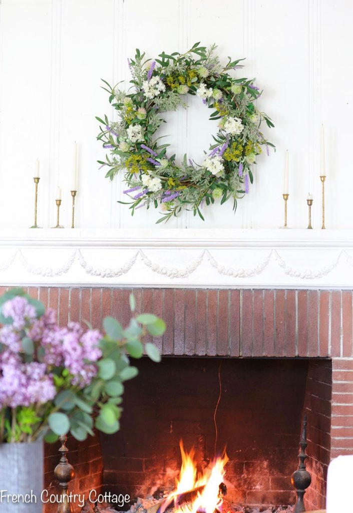 Courtney of French Country Cottage decorating her mantel with a French Market Floral Wreath