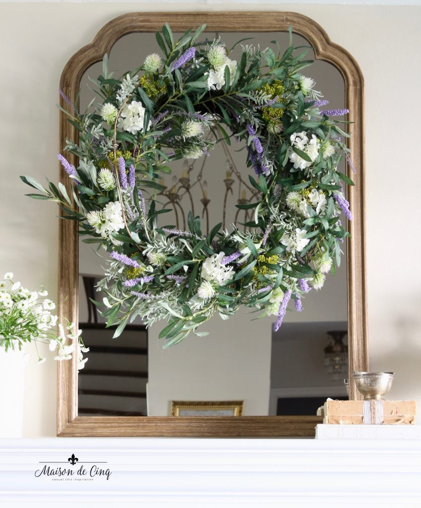 Balsam Hill French Market Floral wreath placed in the center of a mirror frame
