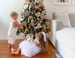 Two children playing with ornaments hung on a Balsam Hill Christmas tree
