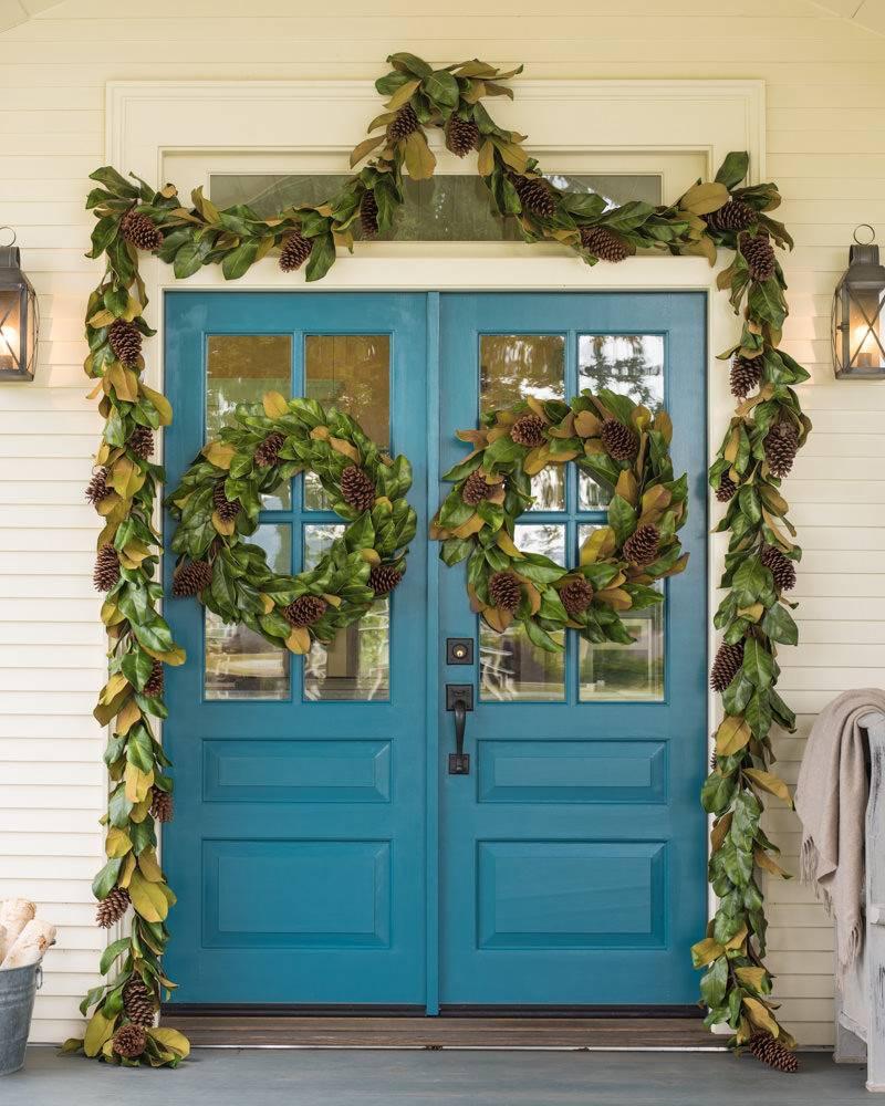 Front door decorated with greenery and pinecones