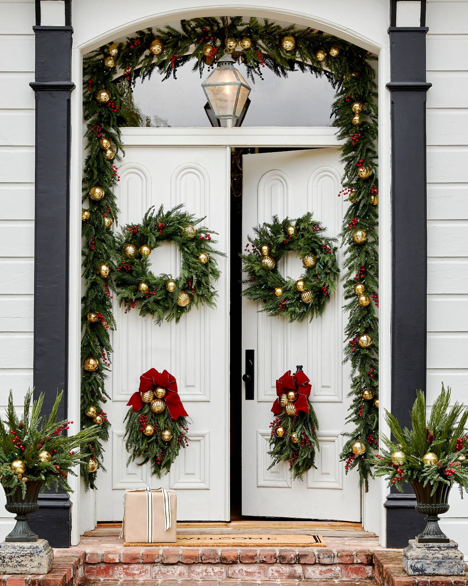 Front door decorated with greenery and gold ornaments
