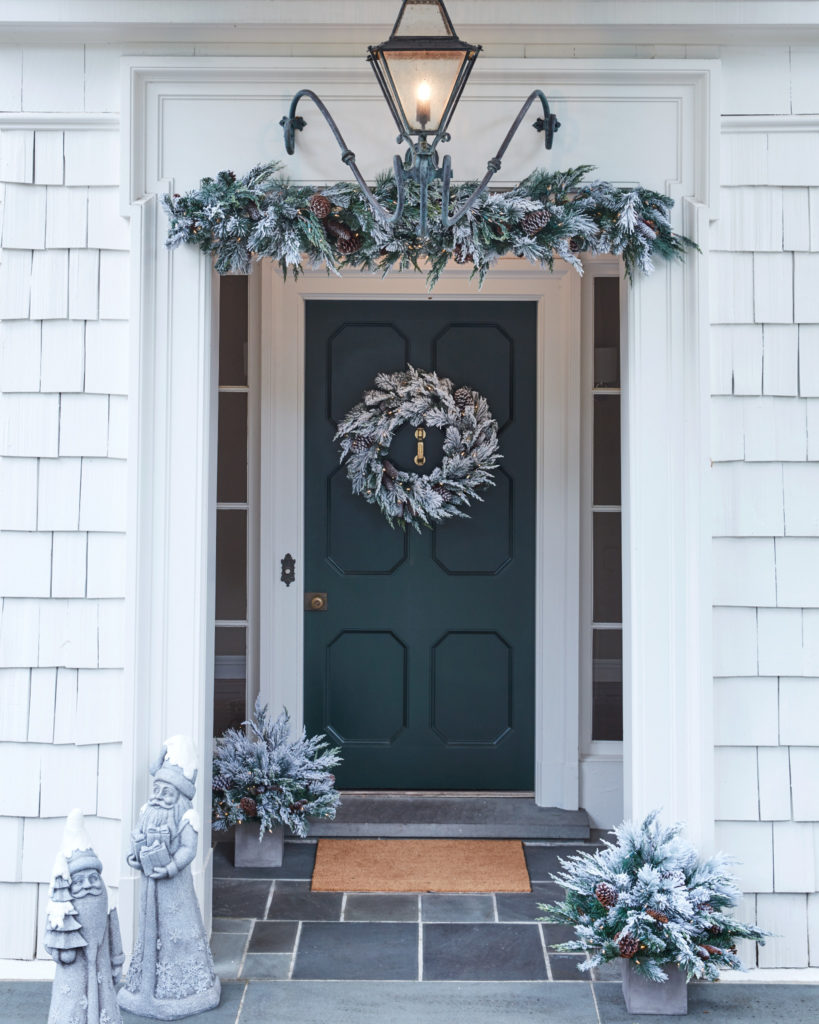 A front door decorated with frosted evergreen foliage