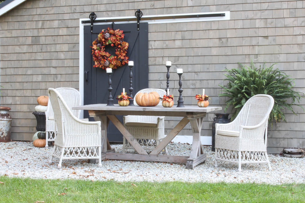 Outdoor dining table set up with pumpkins and candles