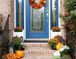 Front steps decorated with greenery and pumpkins