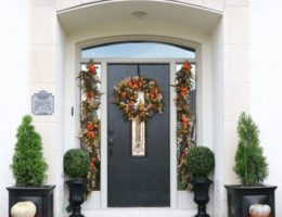 Open entryway decorated with artificial autumn foliage and pumpkins