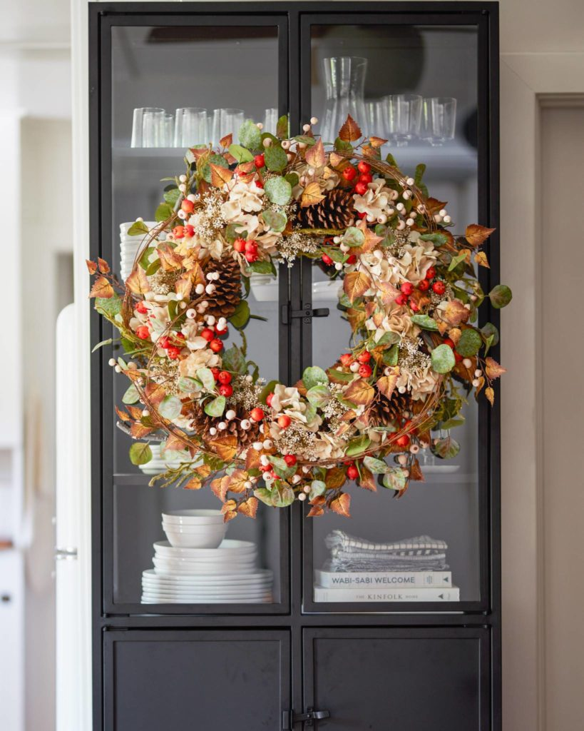 Balsam Hill Briarwood Cottage Artificial Fall Wreath on a cupboard