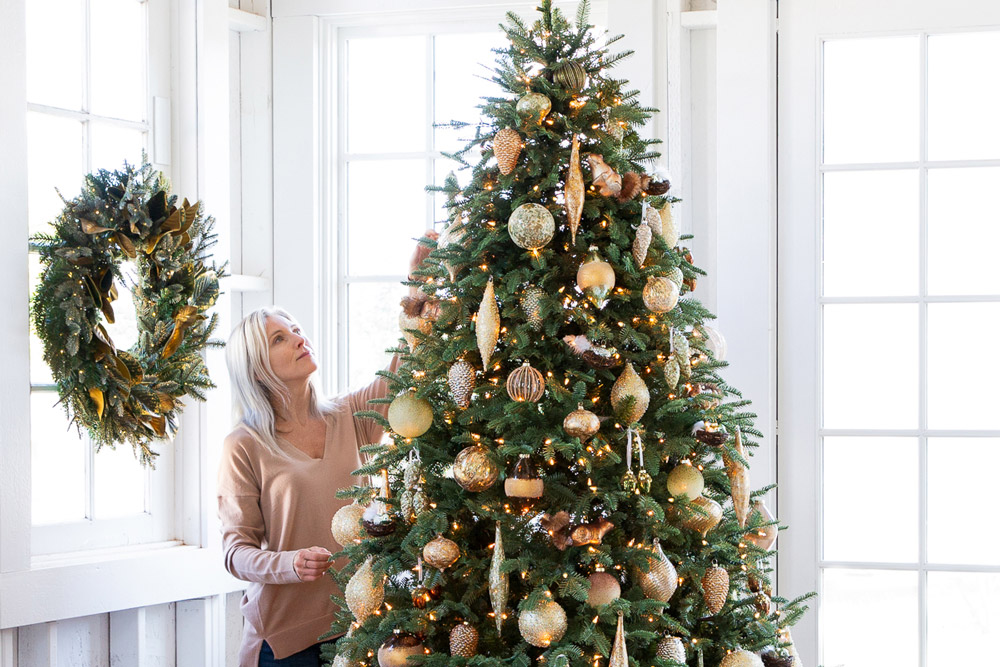 woman decorating realistic artificial Christmas tree