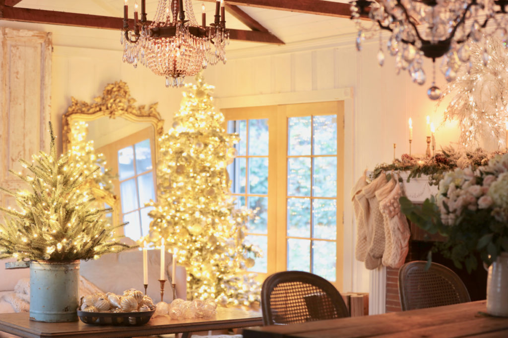 Pre-lit Frosted Yukon Spruce beside French doors and Baby Sanibel Spruce on a coffee table