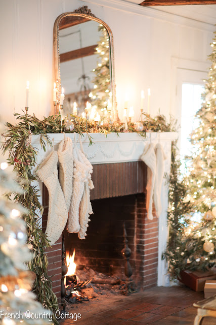 Fireplace mantel decorated with garland, candles, and stockings