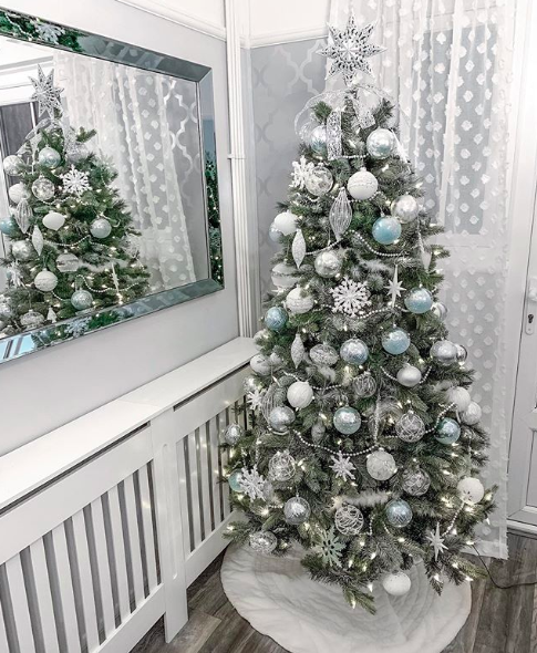 Artificial Christmas tree with silver and blue glittered ornaments