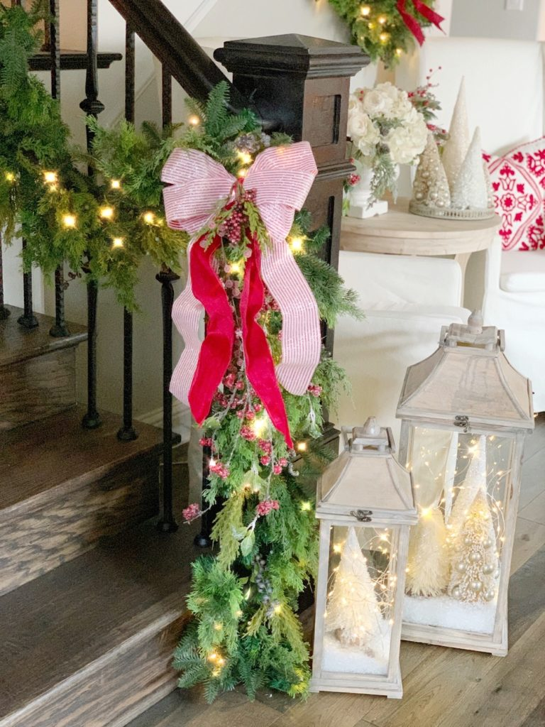 Banister decorated with Outdoor Juniper garland and candy cane ribbon