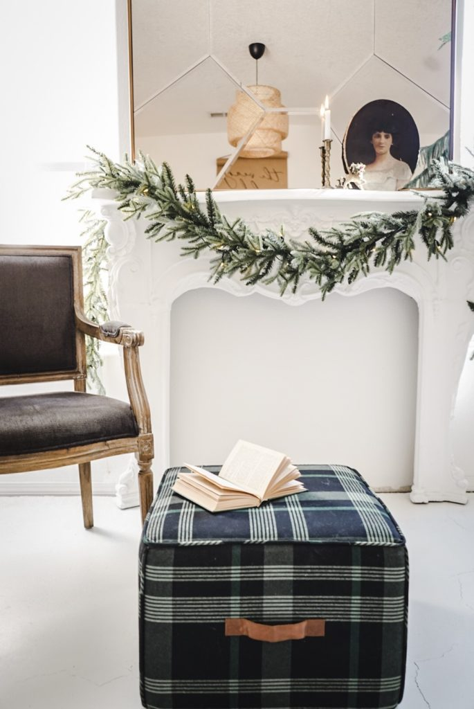Fraser Fir Garland draped over fireplace with brown chair and green plaid ottoman as spring mantel décor ideas